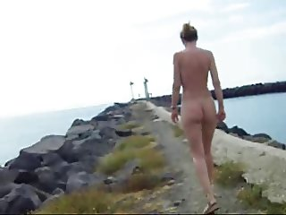Firm titty gal takes a nude walk by the ocean.