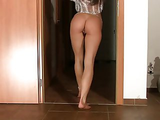 flexible brunette fucks herself in a doorway with a dildo