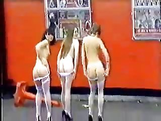 Three Girls Stripping in front of a crowd