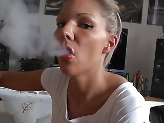 German blonde blowing a big cock while smoking a cigarette