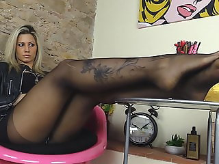 Blonde in leather dress and black pantyhose shows her feet