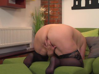 Chubby, blonde granny masturbating on bed.