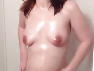 Amateur girl rubs oil on body in the shower