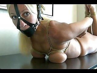 Busty blonde girl tightly tied on table