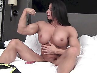 Ripped female bodybuilder fucks a vibrator in bed