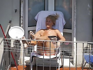 Blonde granny sunbathing on the balcony