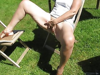 Masturbating hairy pussy in the garden with cars passing by